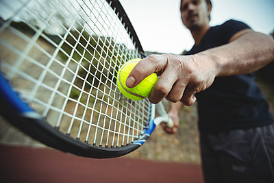 Man with tennis racket ready to serve - p1315m1199466 by Wavebreak