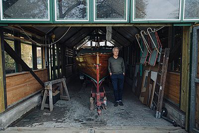 Senior man standing at wooden boat in a boathouse - p300m2155243 by Gustafsson
