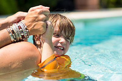 Caucasian mother holding hands of swimming boy - p555m1522781 by Marc Romanelli
