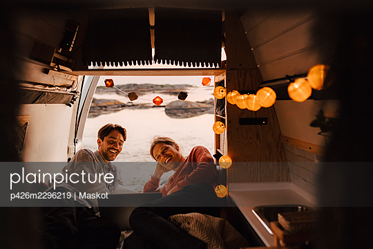 Smiling male friends watching video on laptop in camping van - p426m2296219 by Maskot