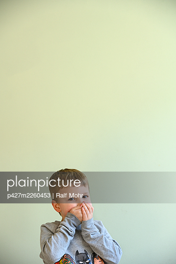 Little boy covering his mouth with hands - p427m2260453 by Ralf Mohr