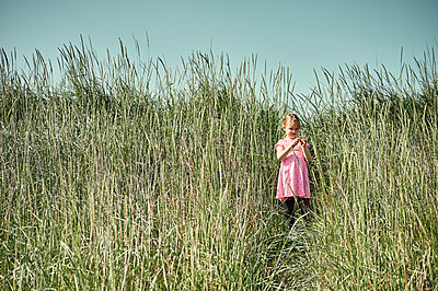 Curious little girl in Icelandic field - p1166m2130732 by Cavan Images