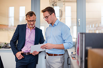 Two businessmen sharing tablet in office - p300m1562522 by Daniel Ingold