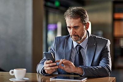 Businessman using smartphone at table - p300m2170952 by Zeljko Dangubic