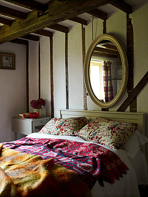 Large mirror above bed with assorted covers in timber framed farmhouse - p349m2167772 by Polly Wreford