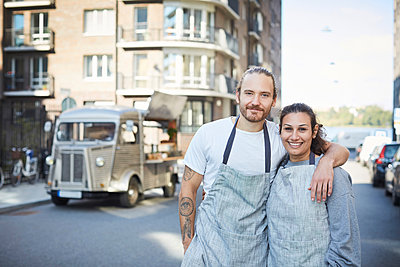 Portrait of confident male and female owners standing arms around with food truck in background - p426m1536957 by Maskot