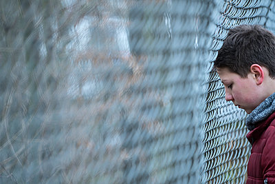 Trauriger Junge an einem Drahtzaun - p427m1548148 von R. Mohr