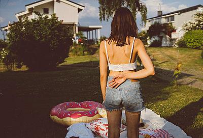 Junge Frau steht nachdenklich im Garten - p432m2230924 von mia takahara