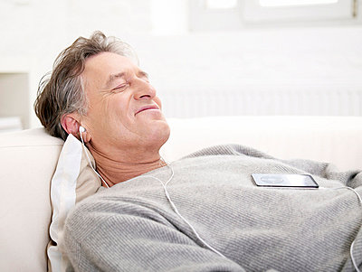 Aelterer Mann hoert Musik mit mp3-Player  - p6430239f von senior images RF