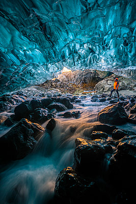 Vatnajokull glacier, Eastern Iceland, Iceland, Northern Europe. Man standing still at the entrance of a a crystal ice cave in winter. - p651m2007292 by Marco Bottigelli