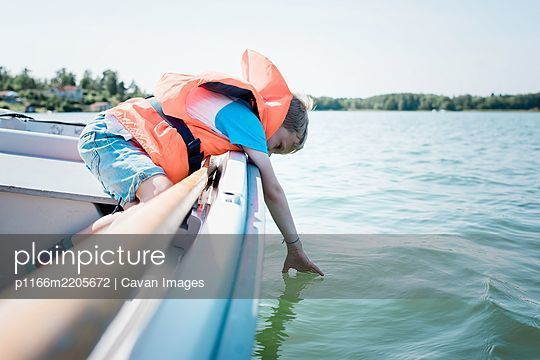 young boy dipping his hands in the water whilst on a boat in summer - p1166m2205672 by Cavan Images