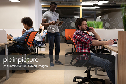 Diverse colleagues using gadgets in office - p1166m2234869 by Cavan Images