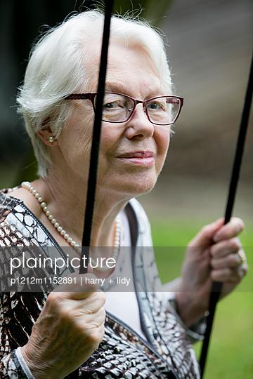 Weißhaarige Frau auf der Schaukel - p1212m1152891 von harry + lidy