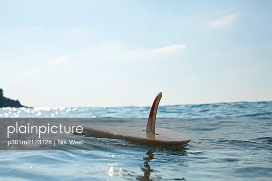 Surfboard floating on sunny blue ocean - p301m2123128 by Nik West