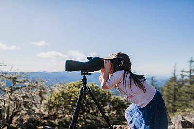 Side view of girl looking through telescope while standing against sky - p1166m1474552 by Cavan Images