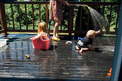 Mom and Children Playing in the Water on the Porch - p1238m1042107 by Amanda Voelker