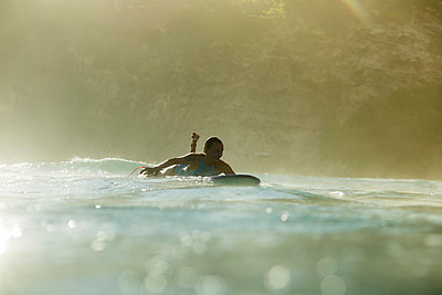 Indonesia, Bali, woman lying on surfboard in the sea - p300m1205181 by Konstantin Trubavin