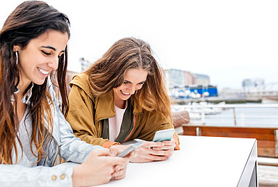 Two happy young women sending messages with their smartphones - p300m1459705 by Marco Govel