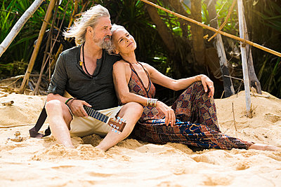 Portrait of happy senior hippie couple with guitar relaxing on the beach - p300m2083974 by Steve Brookland