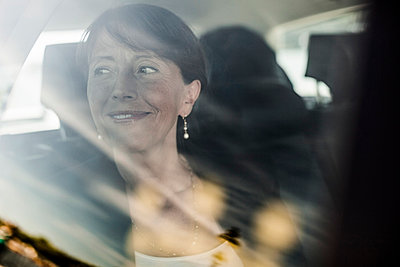 View of businesswoman smiling while looking out through taxi window - p426m844664f by Maskot
