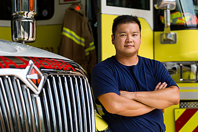 Serious Chinese fireman posing with fire truck - p555m1303353 by Roberto Westbrook