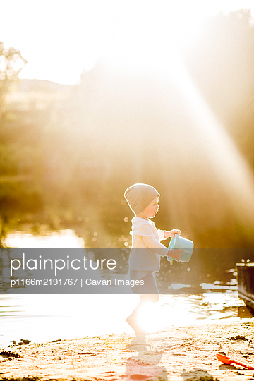 Summer golden sun toddler playing with bucket at lake - p1166m2191767 by Cavan Images