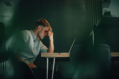 Tired man sitting in office, working late in his start-up company - p300m2029220 von Gustafsson