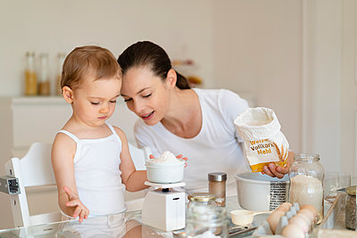 Mother and little daughter making a cake together in kitchen at home weighing flour - p300m2102732 by Daniel Ingold