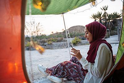 Young tourist woman wearing Hijab at a tent using mobile phone - p300m2206996 by Manu Padilla Photo