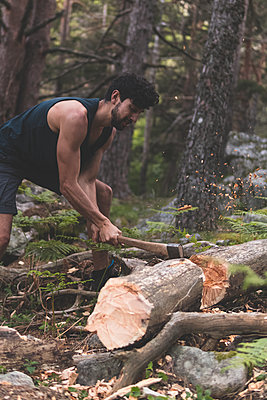 Young man cutting fallen tree trunk with axe in forest - p300m2287732 by Josu Acosta