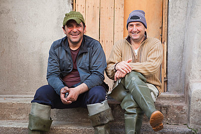 two fisherman sitting on steps, laughing - p4297100 by Judith Haeusler
