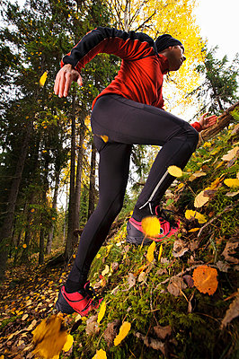 Low angle view of young man jogging in forest - p575m664066 by Hans Berggren