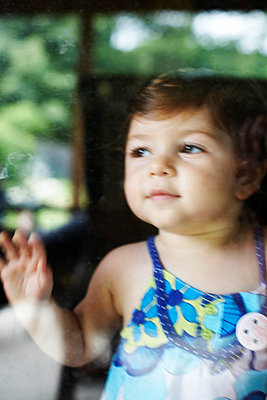 Baby Girl Leaning Against Window - p694m663713 by Maria K