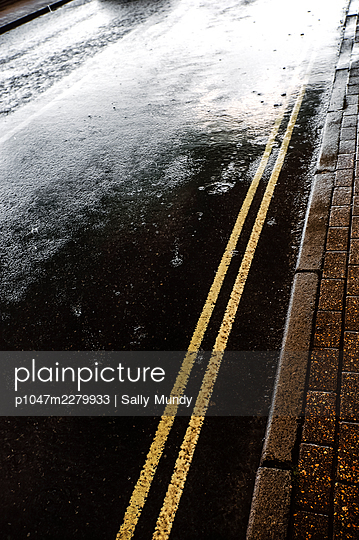 Raindrops on wet tarmac asphalt road surface with double yellow lines next to footpath - p1047m2279933 by Sally Mundy