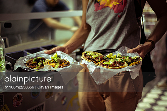 Healthy Mexican taco street food held by strong healthy tourist - p1166m2250656 by Cavan Images