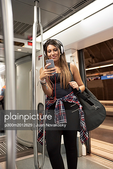Portrait of smiling woman with guitar backpack and headphones looking at cell phone in underground train - p300m2012629 von Juan Novakosky