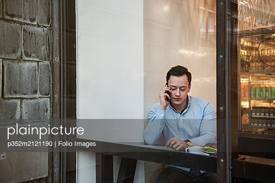 Young man sitting talking on cell phone in a cafe - p352m2121190 by Folio Images