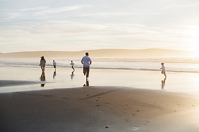 Family running and enjoying against sky during sunset at the beach - p1166m2073867 by Cavan Images