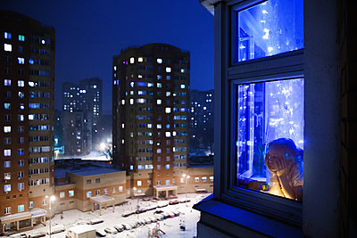 Russia, Moscow, Girl looking out of a window at night - p1642m2216169 by V-fokuse