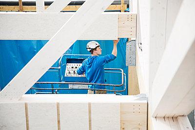 Austria, worker on hoist, positioning roof construction - p300m1567838 by Christian Vorhofer