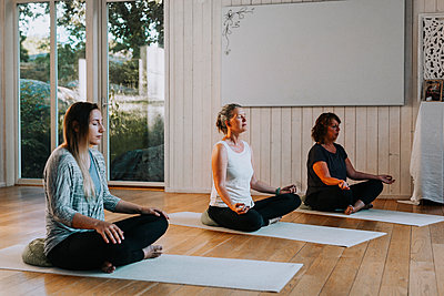 Women meditating in yoga studio - p312m2208271 by Plattform