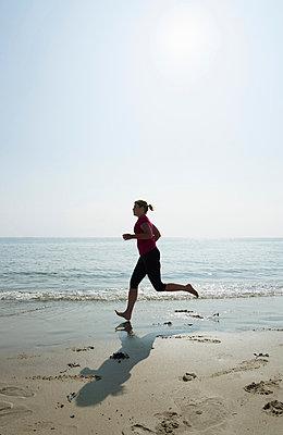 Woman running on beach - p429m821940 by Mischa Keijser