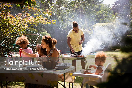 Family barbecuing and eating on sunny summer backyard patio - p1023m2238521 by Tom Merton