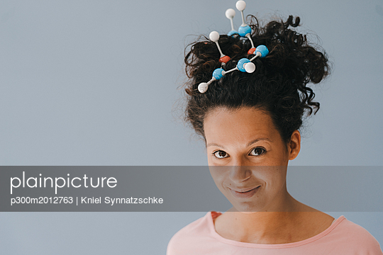 Young woman with molecule model in her hair - p300m2012763 von Kniel Synnatzschke