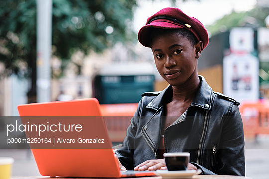 Young woman wearing jacket and cap using laptop while sitting at sidewalk cafe in city - p300m2250164 by Alvaro Gonzalez
