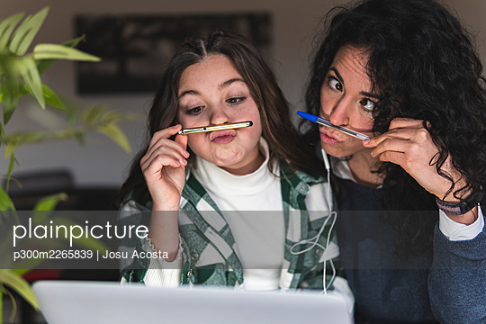 Playful mother and daughter puckering in front of digital tablet at home - p300m2265839 by Josu Acosta