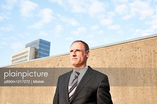 Geschäftsmann vor einer Mauer - p890m1217272 von Mielek