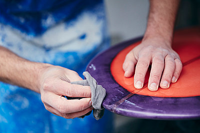 Man sanding and shaping a surfboard in a workshop - p1100m2010435 by Mint Images