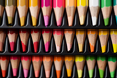 Watercolor pencils lined up in a black plastic box. - p1166m2095592 by Cavan Images