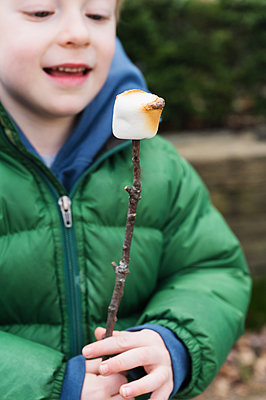 Boy watching roasted marshmallow on stick - p1427m2174028 by Jamie Grill